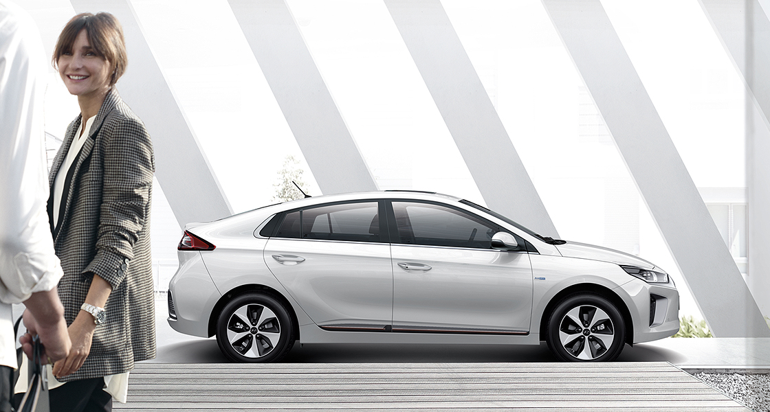Side view of white Ioniq electric and woman standing in front